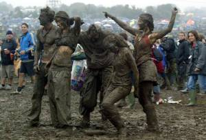 SOMERSET, ENGLAND - JUNE 26: Festival goers dance in the mud in front of the Pyramid stage at Worthy Farm, Pilton, Somerset, at the 2004 Glastonbury Festival, 26 June 2004. The festival spans over 3 days and runs until June 27. (Photo by Matt Cardy/Getty Images)